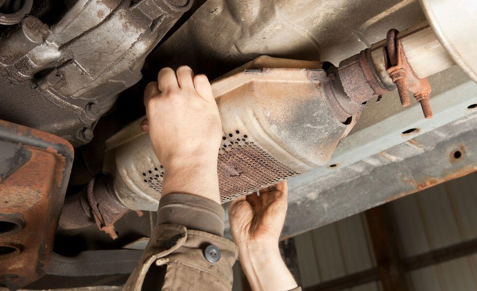 catalytic-converter-removal-at-a-salvage-yard-royalty-free-image-1615767464_.jpg